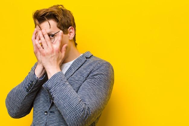 Junger roter hauptmann, der erschrocken oder verlegen sich fühlt, mit den augen späht oder ausspioniert, die mit den händen halb bedeckt werden, die orange sind