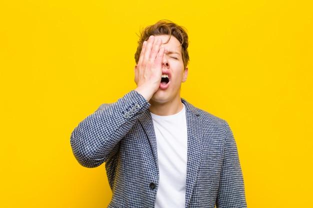 Junger roter hauptmann, der schläfrig, gelangweilt und gähnend schaut, wenn kopfschmerzen und eine hand die hälfte des gesichtes bedecken