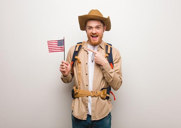 Junger rothaarigeforschermann, der auf die seite mit dem finger zeigt. hält eine flagge der vereinigten staaten.
