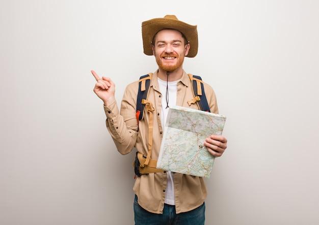 Junger rothaarigeforschermann, der auf die seite mit dem finger zeigt. hält eine karte.