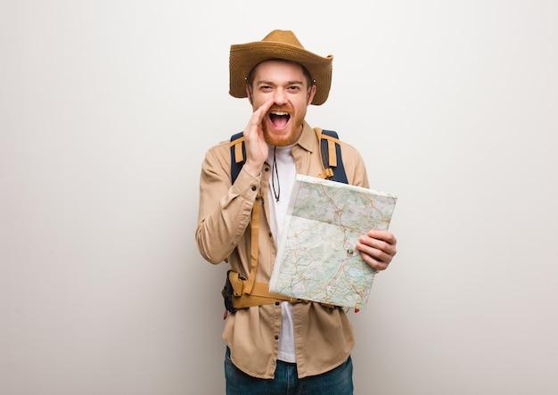 Junger rothaarigeforschermann, der etwas glücklich zur front schreit. hält eine karte.