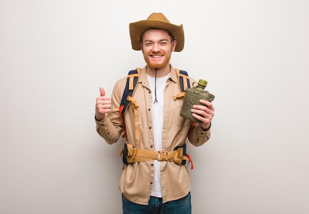 Junger rothaarigeforschermann, der oben daumen lächelt und anhebt. er hält eine kantine.