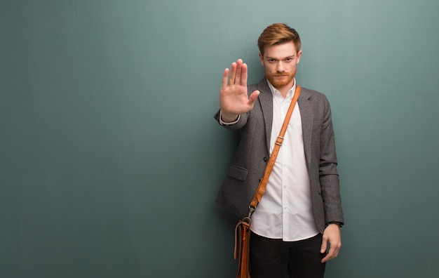Junger rothaarigegeschäftsmann, der hand in front einsetzt