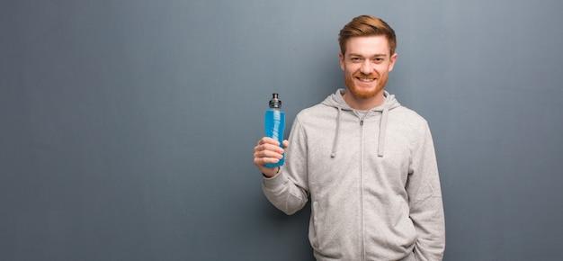 Junger rothaarigeignungsmann nett mit einem großen lächeln. er hält einen energy drink in der hand.