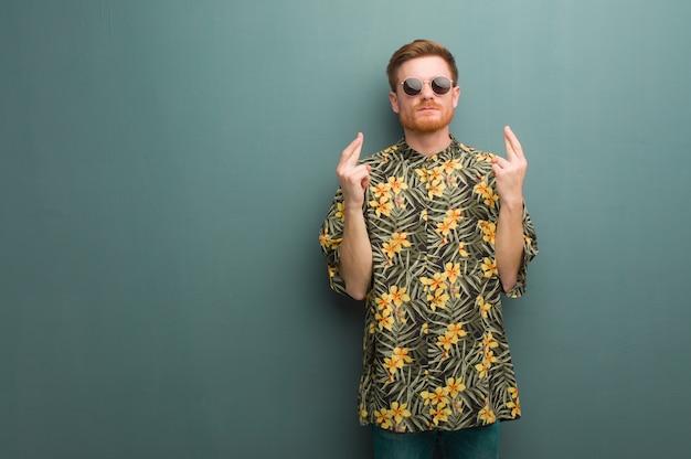 Junger rothaarigemann, der die exotische sommerkleidung kreuzt finger für das haben des glücks trägt