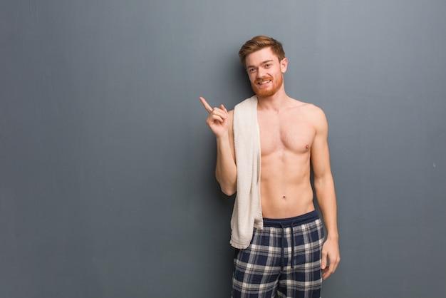 Junger rothaarigemann, der ein tuch zeigt auf die seite mit dem finger hält. er hält ein weißes handtuch.