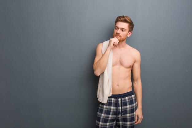 Junger rothaarigemann, der ein tuch zweifelhaft und verwirrt hält. er hält ein weißes handtuch.