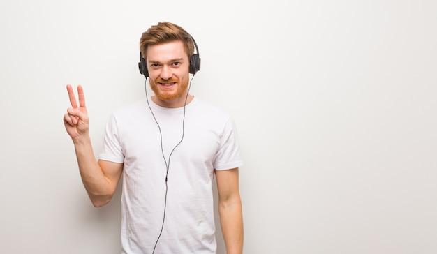 Junger rothaarigemann, der nummer zwei zeigt. musik mit kopfhörern hören.