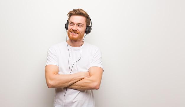 Junger rothaarigemann, der überzeugt lächelt und die arme, oben schauend kreuzt. musik mit kopfhörern hören.