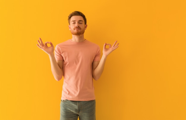 Junger rothaarigemann, der yoga durchführt