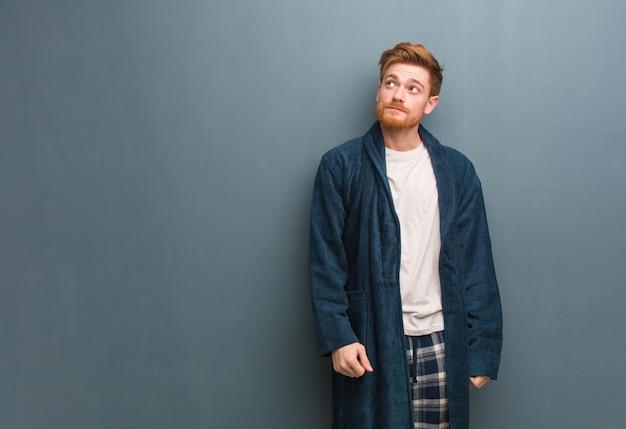 Junger rothaarigemann im pyjama träumend vom erreichen von zielen und von zwecken