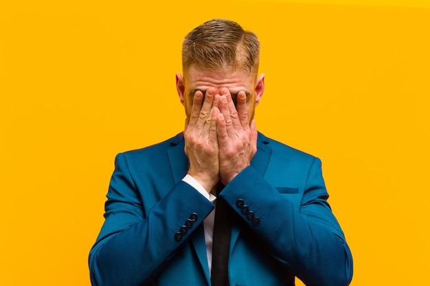 Junger rothaariger geschäftsmann, der traurig, frustriert, nervös und deprimiert fühlt, gesicht mit beiden händen bedeckt und gegen orange hintergrund weint