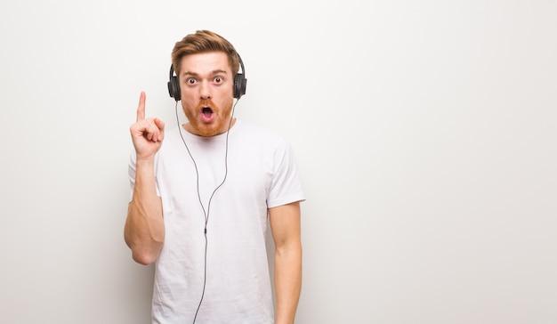 Junger rothaariger mann, der eine große idee, konzept der kreativität hat. musik hören mit kopfhörern.