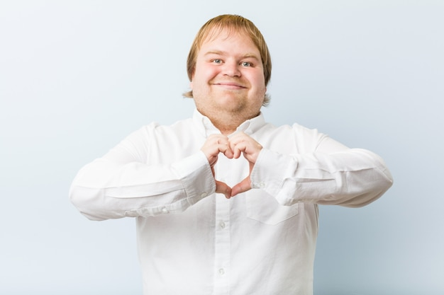 Junger rothaariger mann, der eine herzform mit den händen lächelt und zeigt