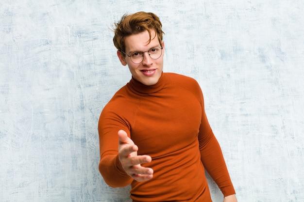 Junger rothaariger mann, der lächelt, glücklich, zuversichtlich und freundlich aussieht, einen handschlag anbietet, um einen deal abzuschließen, der an der schmutzwand zusammenarbeitet