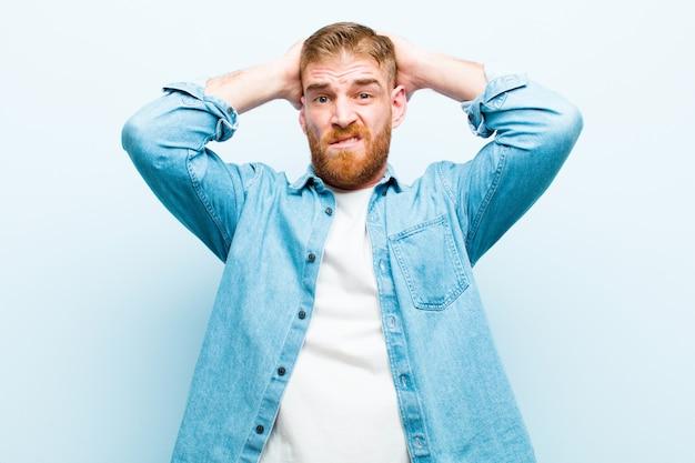 Junger rothaariger mann, der sich frustriert und genervt fühlt, krank und müde vom versagen, satt von langweiligen, langweiligen aufgaben über weicher blauer wand