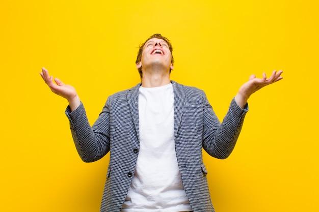 Junger rothaariger mann, der sich glücklich, erstaunt, glücklich und überrascht fühlt und den sieg mit beiden händen in der luft auf orange feiert