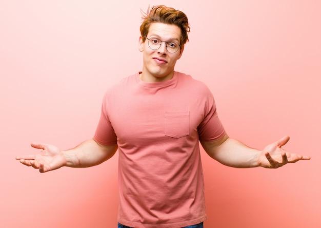 Junger rothaariger mann, der sich verwirrt und verwirrt fühlt, unsicher über die richtige antwort oder entscheidung, versucht, eine wahl gegen rosa wand zu treffen