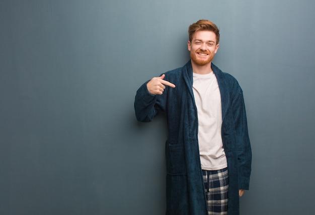 Junger rothaariger mann in der pyjama-person, die von hand auf einen hemdkopierraum zeigt, stolz und zuversichtlich