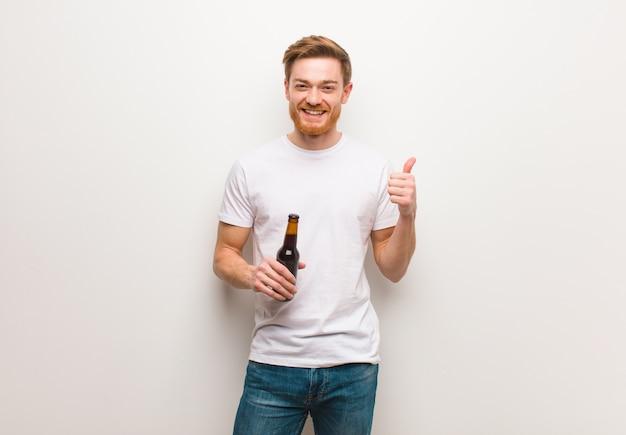 Junger rothaariger mann lächelt und hebt daumen hoch. ein bier halten.