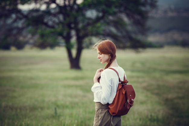 Junger rothaariger reisender in märchenhafter schöner landschaft