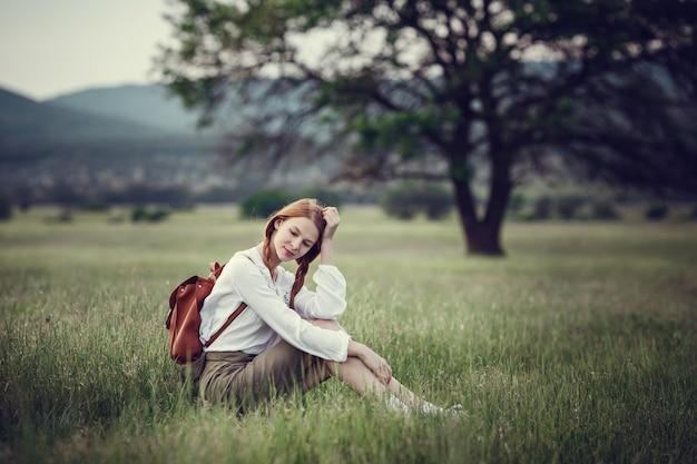Junger rothaariger reisender in märchenhafter schöner landschaft.