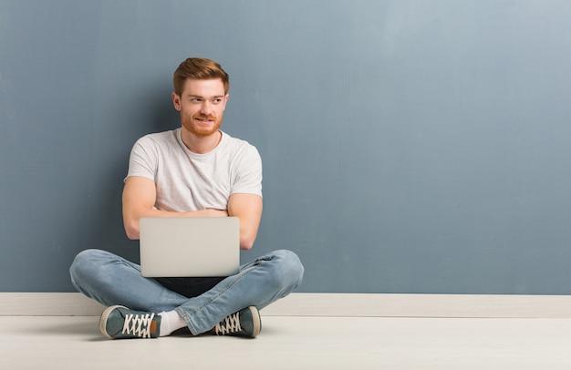 Junger rothaariger studentenmann, der auf dem boden sitzt, der selbstbewusst lächelt und arme verschränkt, aufblickend. er hält einen laptop in der hand.