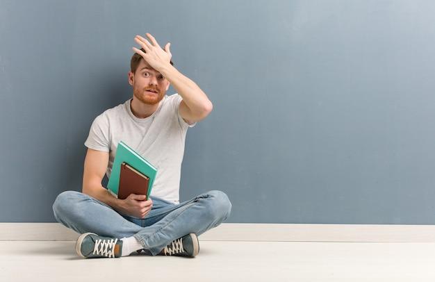 Junger rothaariger studentenmann, der besorgt und überwältigt auf dem boden sitzt. er hält bücher.