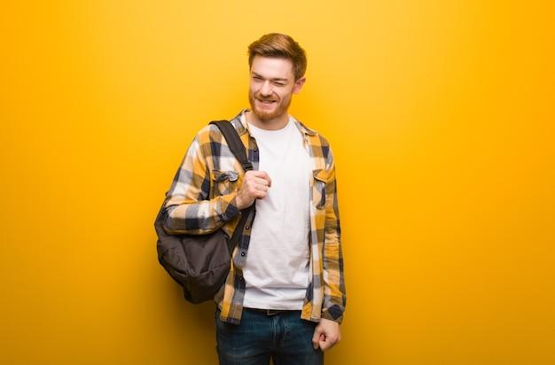 Junger rothaariger studentenmann zwinkert, lustig, freundlich und sorglose geste
