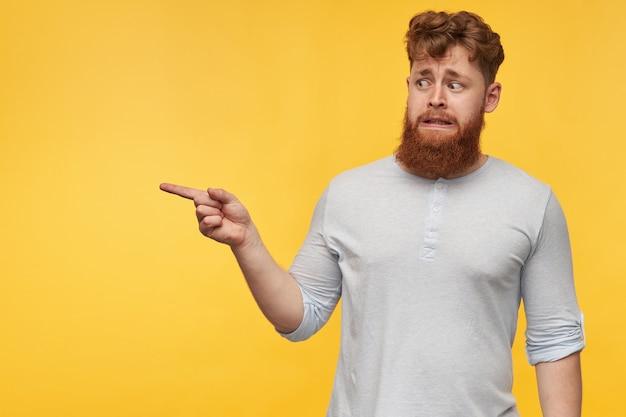 Junger rothaariger typ mit einem großen roten bart, der sich gereizt und verwirrt fühlt, zeigt mit einem finger in einen kopierraum