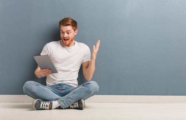 Junger rothaarigestudentenmann, der auf dem boden feiert einen sieg oder einen erfolg sitzt. er hält eine tablette in der hand.