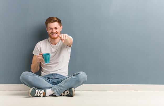 Junger rothaarigestudentenmann, der auf dem boden nett und lächelnd sitzt, zeigend auf front.