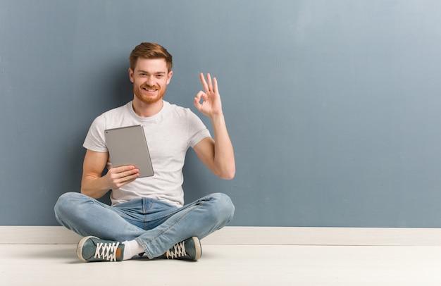 Junger rothaarigestudentenmann, der auf dem boden nett und überzeugt sitzt, okaygeste tuend. er hält eine tablette in der hand.