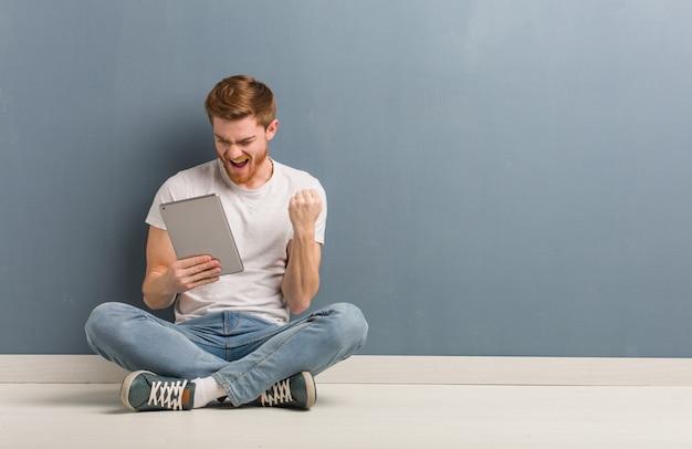 Junger rothaarigestudentenmann, der auf dem boden überrascht und entsetzt sitzt. er hält eine tablette in der hand.