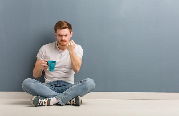 Junger rothaarigestudentenmann, der auf dem boden zeigt faust zur front, verärgerter ausdruck sitzt. er hält eine kaffeetasse in der hand.