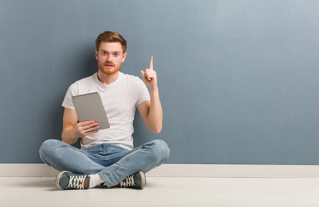Junger rothaarigestudentenmann, der auf dem boden zeigt nummer eins sitzt. er hält eine tablette in der hand.