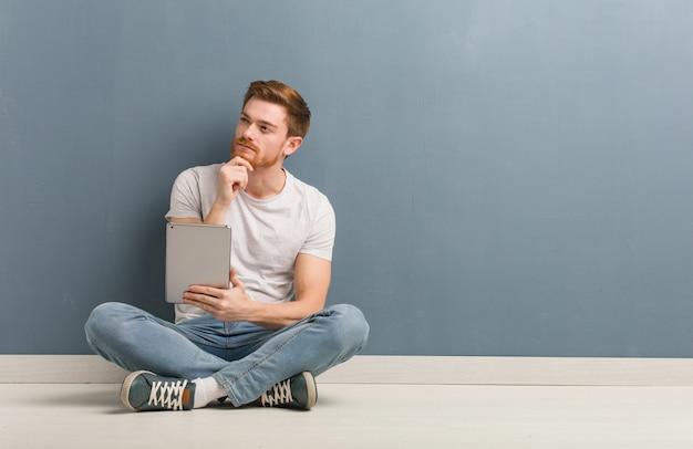 Junger rothaarigestudentenmann, der auf dem boden zweifelnd und verwirrt sitzt. er hält eine tablette in der hand.