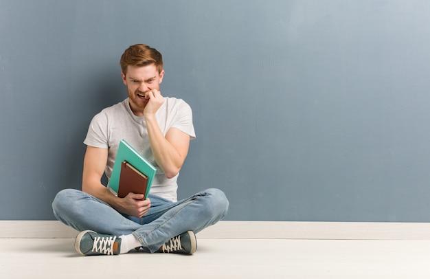 Junger rothaarigestudentenmann, der auf den beißenden nägeln des bodens, nervös und sehr besorgt sitzt. er hält bücher.