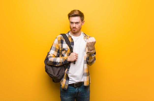Junger rothaarigestudentenmann, der der front faust, verärgerter ausdruck zeigt