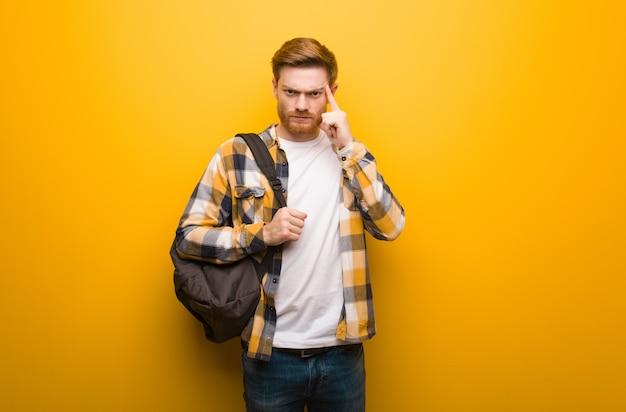 Junger rothaarigestudentenmann, der eine konzentrationsgeste tut