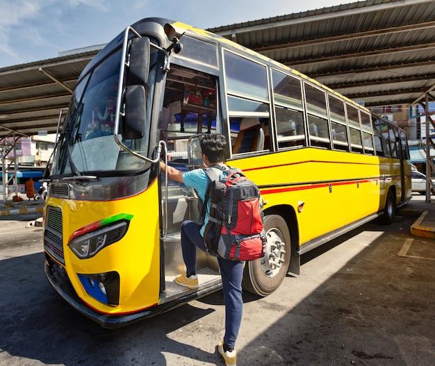 Junger rucksackreisender, der in bus einsteigt. lokalbus in der provinz karnchanaburi, thailand.