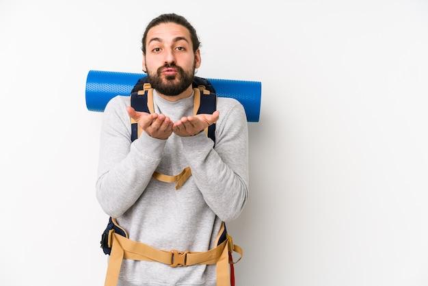Junger rucksacktourist mann isoliert auf weißen faltlippen und hält handflächen, um luftkuss zu senden.