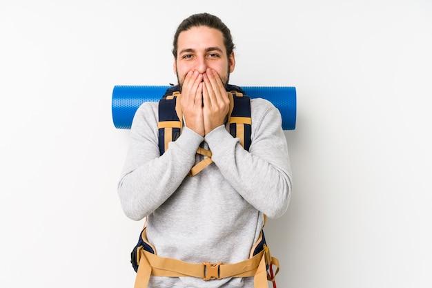 Junger rucksacktourist mann lokalisiert auf einem weißen hintergrund, der über etwas lacht und mund mit händen bedeckt.