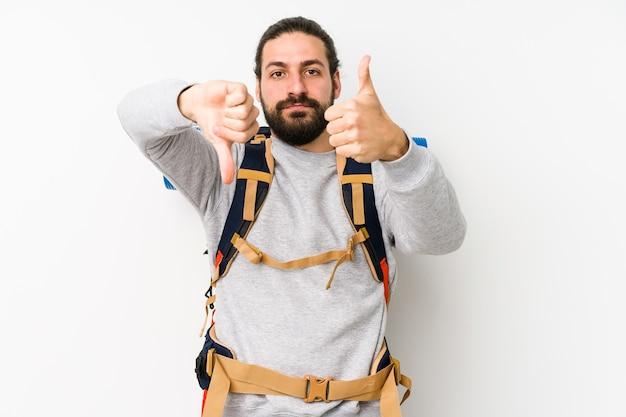 Junger rucksacktourist mann lokalisiert auf einer weißen wand, die daumen hoch und daumen runter zeigt, schwieriges auswahlkonzept
