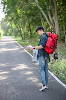 Junger rucksacktourist reisender mit karte, er trägt einen großen rucksack beim entspannen im freien in den sommerferien im waldversuch, kopierraum