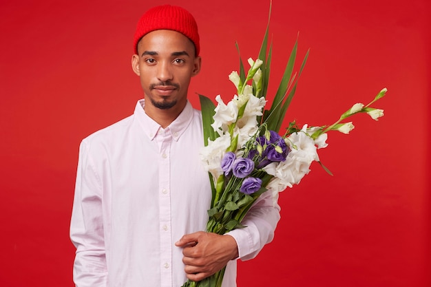 Junger ruhiger afroamerikaner kerl im weißen hemd und im roten hut, hält blumenstrauß, steht über rotem hintergrund und schaut in die kamera.