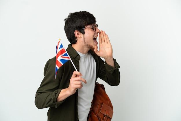 Junger russischer mann, der eine britische flagge isoliert auf weißem hintergrund hält und mit weit geöffnetem mund zur seite schreit
