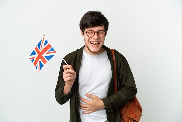 Junger russischer mann, der eine flagge des vereinigten königreichs isoliert auf weißem hintergrund hält und viel lächelt