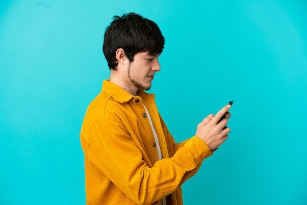Junger russischer mann isoliert auf blauem hintergrund, der eine nachricht oder e-mail mit dem handy sendet