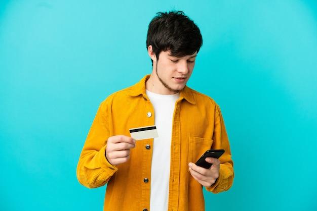 Junger russischer mann isoliert auf blauem hintergrund, der mit dem handy mit einer kreditkarte kauft?